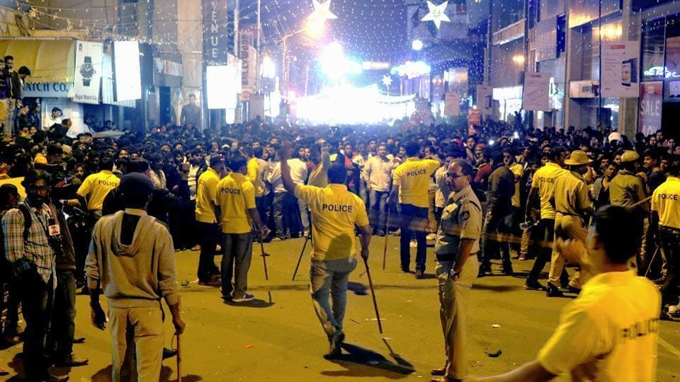 Policemen attempt to manage crowds during New Year's eve celebrations in Bengaluru on December 31, 2016.