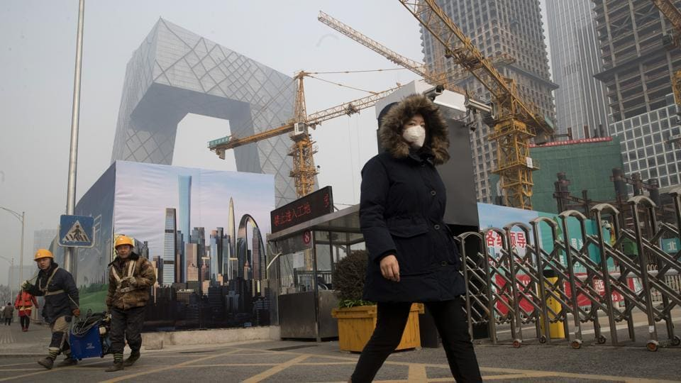 A woman wearing a mask walks past a construction site as smog continues to choke Beijing on Friday, Jan. 6, 2017.