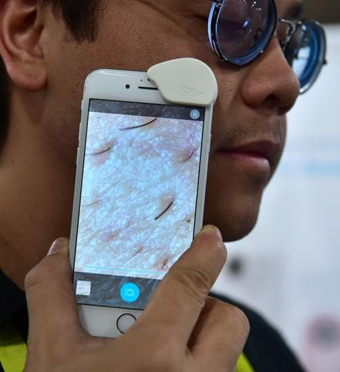 A man demonstrates the SkinScopy smartphone skin analyzer from iOB (Internet of Beauty) Labs during the 2017 Consumer Electronic Show (CES) at the Las Vegas Convention Center in Las Vegas, Nevada. (AFP)
