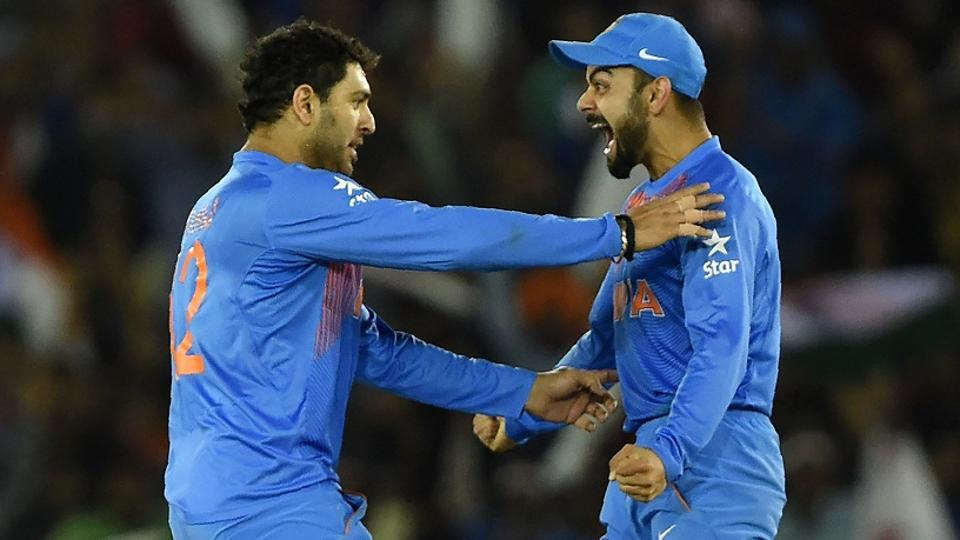 Vuvraj Singh celebrates with teammate Virat Kohli after the dismissal of Australia's Steve Smith during the World T20 match between India and Australia in Mohali on March 27, 2016.
