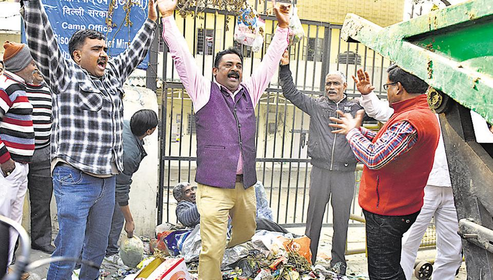 Dozens of municipal workers dumped garbage and shouted slogans outside Deputy CM Manish Sisodia's camp office in New Delhi on Friday.