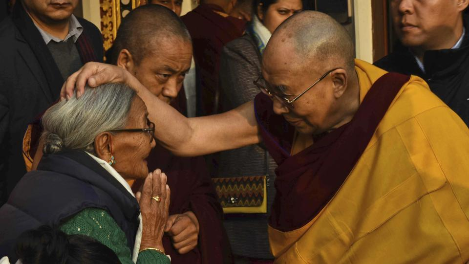 Tibetan spiritual leader the Dalai Lama put his hand on an elderly devotee during the fourth day of Kalachakra in Bodhgay on Thursday. (AP/AP Photo/Manish Bhandari)