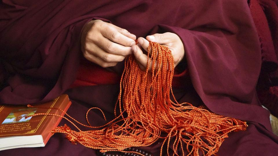A Buddhist monks sits with prayer beads during the fourth day of Kalachakra in Bodhgaya of Bihar on Thursday. Buddhist devotees from across the globe have arrived in this small town to attend the 'Kalachakra' or Wheel of Time initiations by the Dalai Lama. (AP Photo/Manish Bhandari)