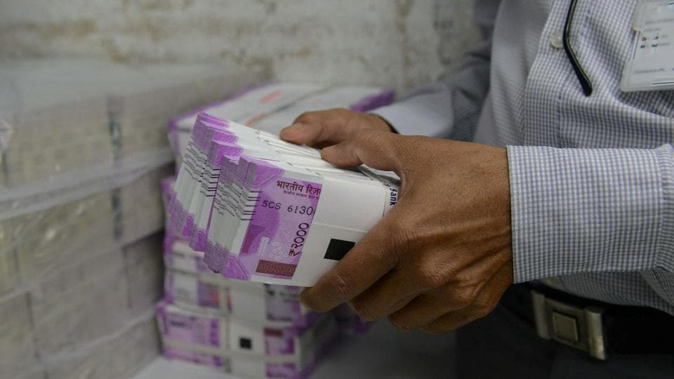 An Indian bank employee checks stacks of new 2000 rupee notes in Ahmedabad on November 11, 2016. Long queues formed outside banks in India as people crowded in to deposit old currency and withdraw new notes after the two largest denomination rupee notes were taken out of circulation. / AFP PHOTO / SAM PANTHAKY