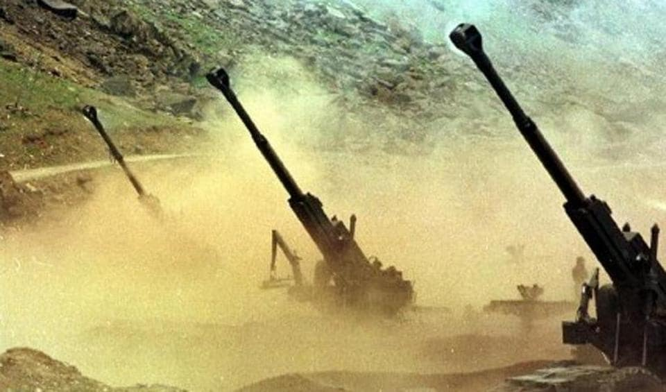 Indian artillery men fire 155mm Bofors guns at enemy positions from a gun emplacement in the Drass sector of Indian-controlled Kashmir 22 June 1999.