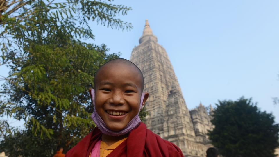 A young Buddhist monk smiles as he arrives to pray at the Mahabodhi temple where the Buddha is said to have attained enlightenment. (AFP PHOTO / Dibyangshu SARKAR)