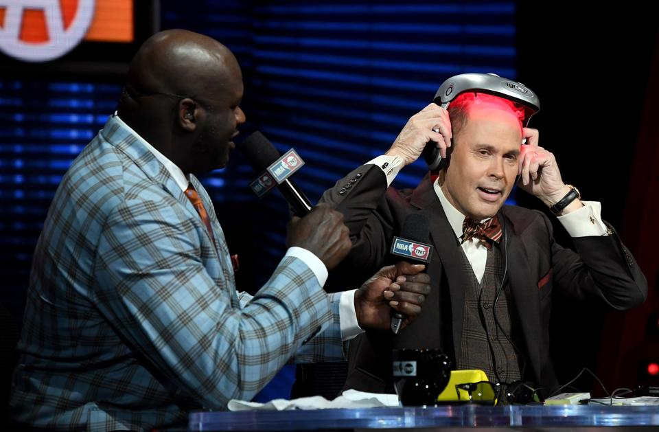 NBA analyst Shaquille O'Neal (L) looks on as TNT's Inside the NBA host Ernie Johnson puts on an iGrow laser-based hair-growth helmet during a live telecast of