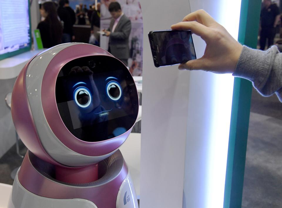 An attendee records images of a prototype Kikoo autonomous robot for children made by Hanwuji Intelligence at CES 2017 at the Sands Expo and Convention Center in Las Vegas, Nevada. The $600 robot features facial recognition technology and is designed to be a companion to children when their parents are working. Using age-based interactive content, it can launch talks or songs actively and dance or play with children as well as automatically take photos and video using voice or app instruction.  (AFP)
