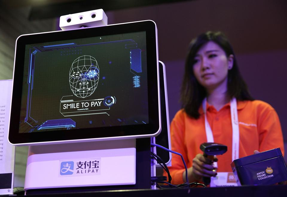 An Alibaba employee demonstrates 'Smile to Pay', an automatic payment system that authorize payment via facial recognition, at the Alibaba booth during CES 2017 at the Las Vegas Convention Center in Las Vegas. (AFP)