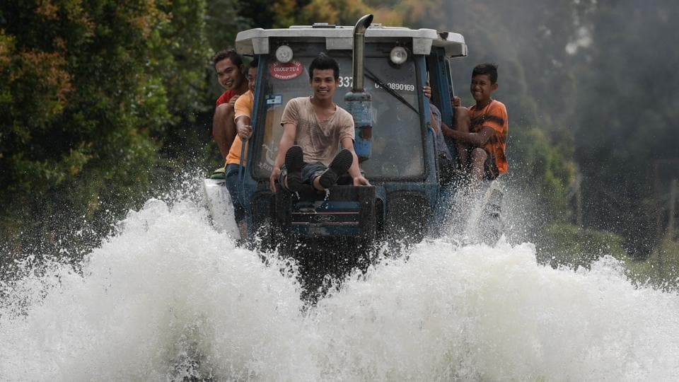 Local residents use a tractor to drive through floodwaters in Jal Besar, Malaysia's northeastern town of Tumpat on January 5, 2017.  (MOHD RASFAN/ / AFP)