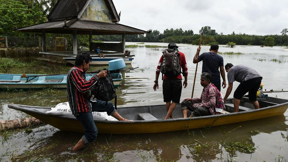 Local residents use a rental boat at the edge of floodwaters in Bendang Pak Yong, Malaysia's northeastern town of Tumpat, which borders with Thailand on January 6, 2017.  (MOHD RASFAN / AFP)