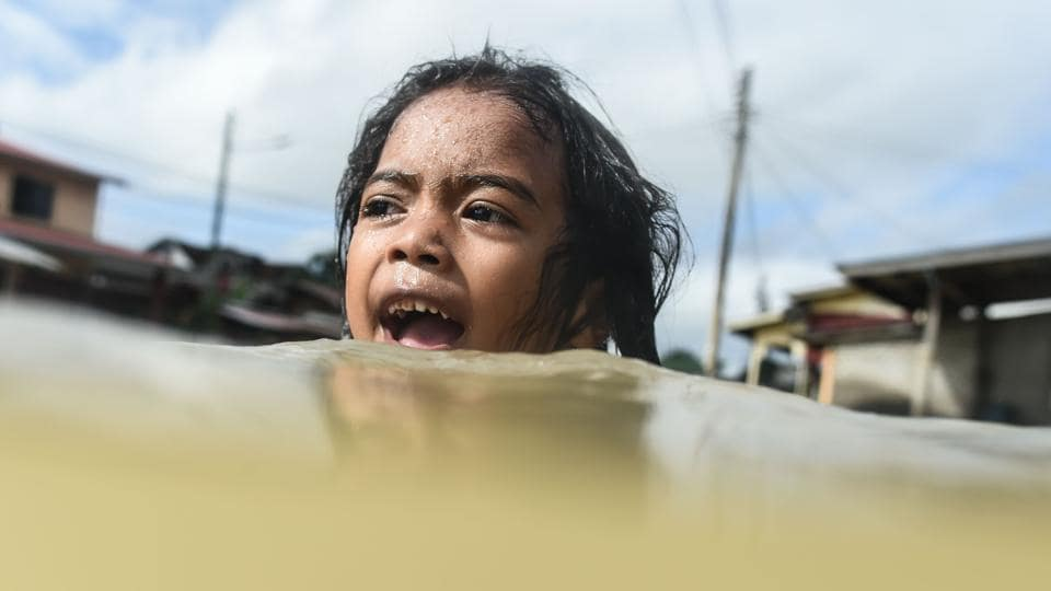 A girl swims in floodwaters in Malaysia's northeastern town of Rantau Panjang, which borders Thailand, on January 5, 2017.  (MOHD RASFAN/ AFP)