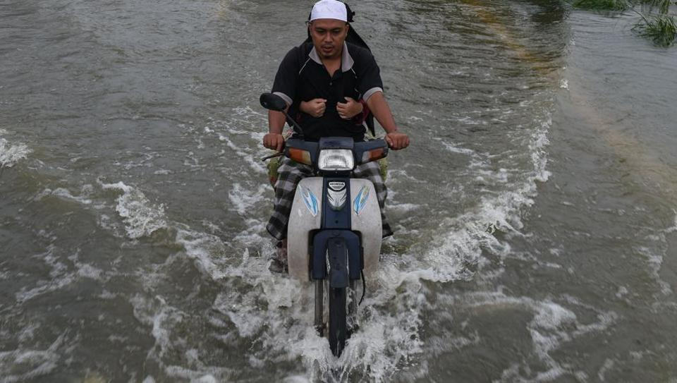 A local resident rides a motorcycle with his wife through floodwaters in Jal Besar, Malaysia's northeastern town of Tumpat, which borders Thailand on January 6, 2017. (MOHD RASFAN / AFP)