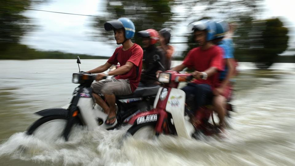 Motorcyclists ride through floodwaters in Jal Besar, Malaysia's northeastern town of Tumpat, on January 5, 2017. Floods continued to inundate two northeast Malaysian states on January 5, as thousands of people remained in relief centres while others expressed fears of looting and sought aid.  (MOHD RASFAN / AFP)