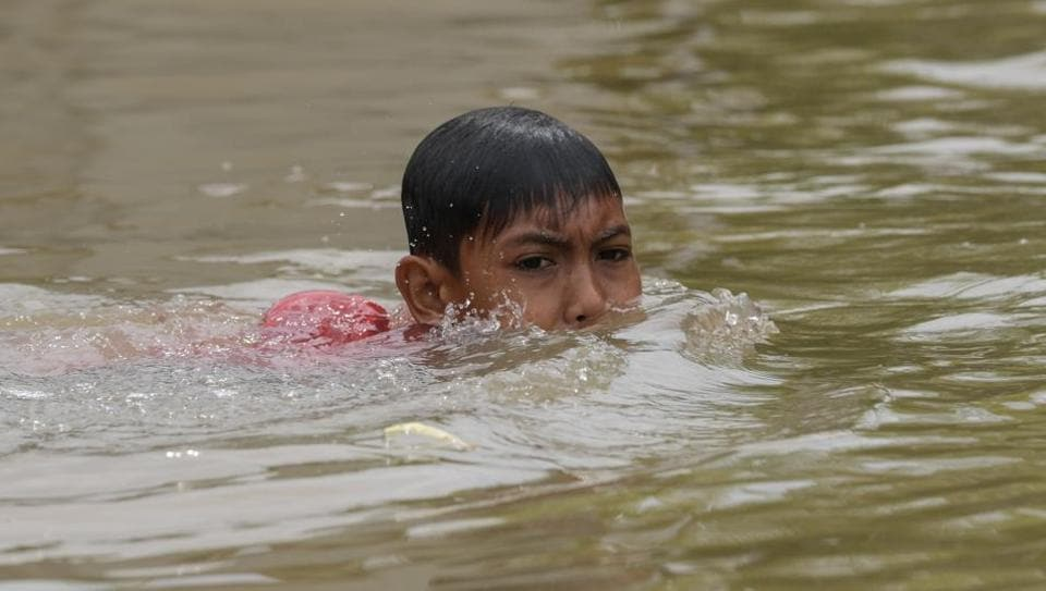 A child swims in floodwaters in Bendang Pak Yong, Malaysia's northeastern town of Tumpat, which borders with Thailand on January 6, 2017.  (MOHD RASFAN / AFP)