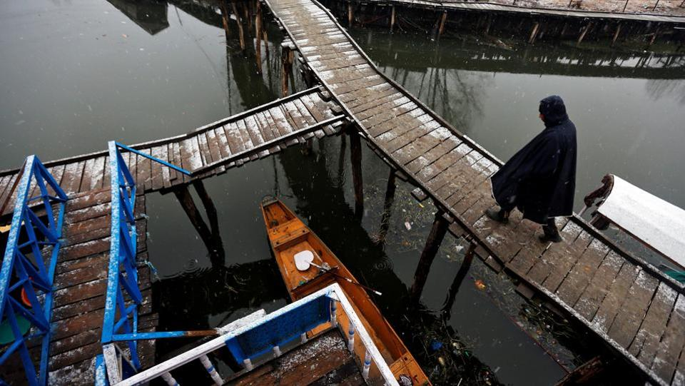 A man walks on a footbridge at Dal Lake during a snowfall on a cold winter morning in Srinagar January 4, 2017.  (Danish Ismail / REUTERS)