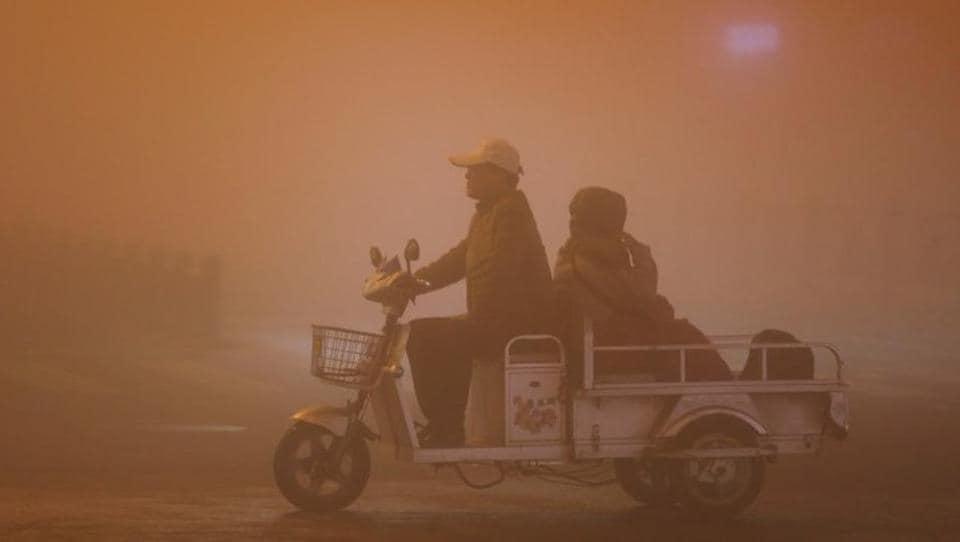 People ride during heavy smog in Lianyungang, Jiangsu province, China.