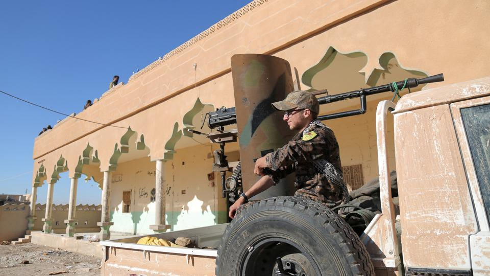 A Syrian Democratic Forces (SDF) fighter sits on the back of a pick-up truck with a weapon installed on it, in Tal Samin village, north of Raqqa city, Syria.