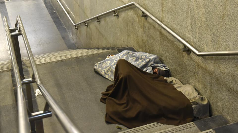 People seek refuge from the cold on the stairs of the AIIMS metro station. (Saumya Khandelwal/HT PHOTO)