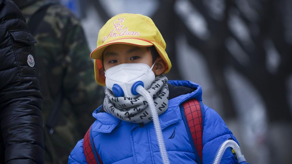 A boy wears a mask as he walks along road in Beijing on Thursday.