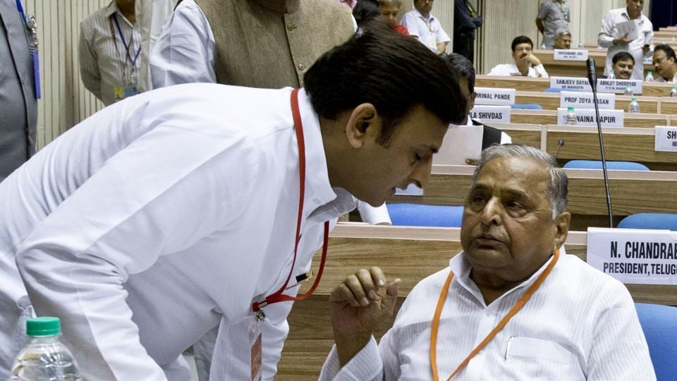 This file photograph taken on September 23 shows CM Akhilesh Yadav (L) listening to his father Mulayam Singh during the Indian National Integration Council meeting in New Delhi.
