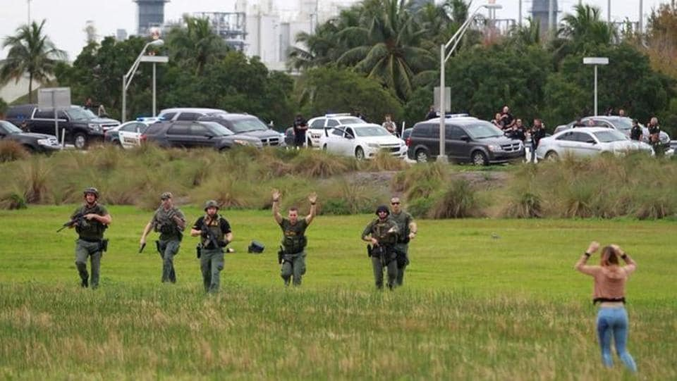 Law enforcement officers move in to verify the identity of people in this field just outside the airport perimeter following a shooting incident at Fort Lauderdale-Hollywood International Airport in Fort Lauderdale.