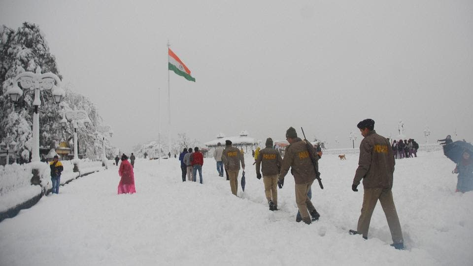 Police personnel walk across the snow-covered historical site 'The Ridge'. (PTI)