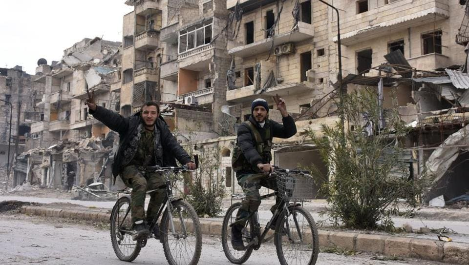 Syrian regime forces flash the victory sign in the former rebel-held Sukkari district in the northern city of Aleppo.