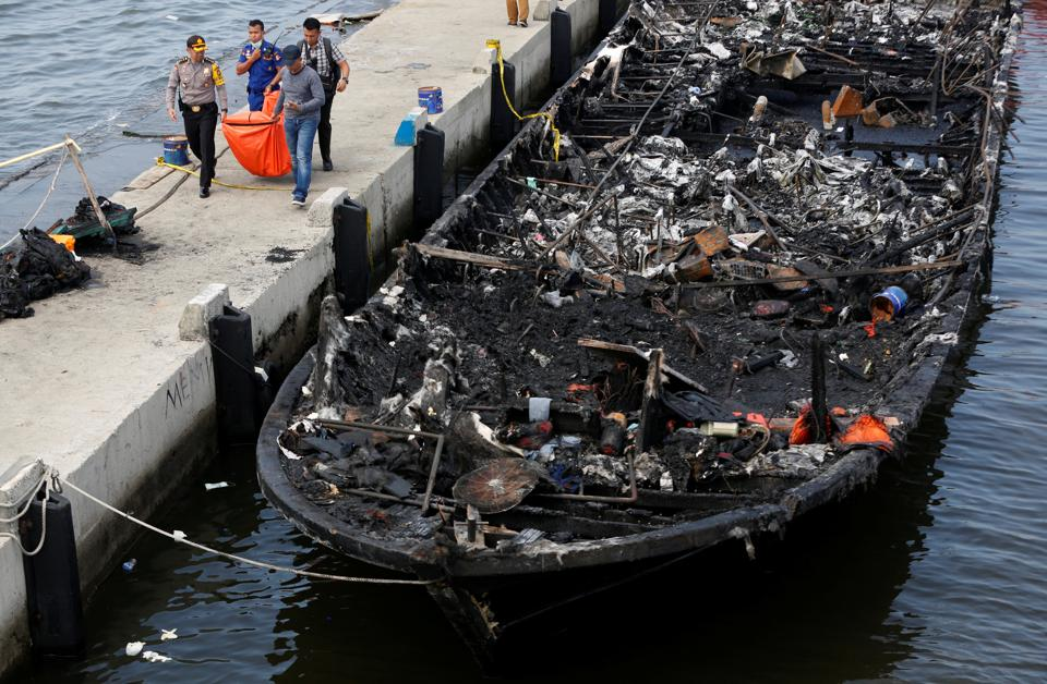 The remains of a victim is carried away after a fire ripped through a boat carrying tourists to islands north of the capital at Muara Angke port in Jakarta on January 1.  (REUTERS)