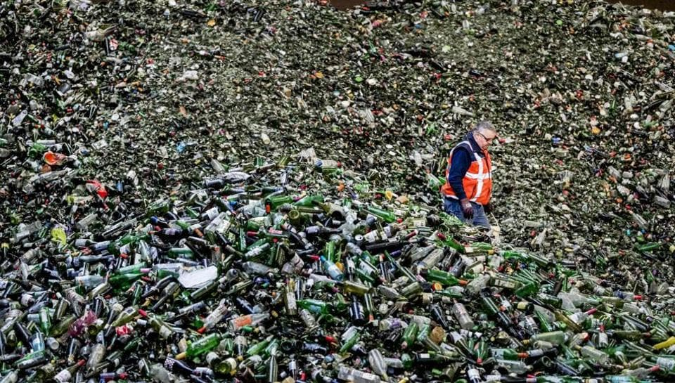 A man stands among bottles at the Van Tuijl glass recycling plant following Christmas and New Year celebrations in Gameren, the Netherlands, on January 3. (AFP)