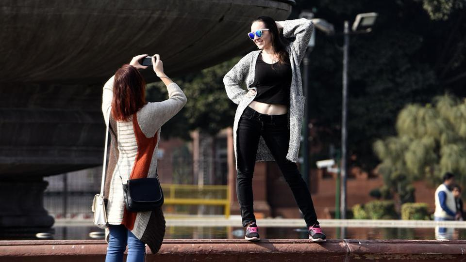 Foreign tourists click photos and enjoying the weather at Vijay chowk, in New Delhi January 04.  (Sonu Mehta/HT PHOTO)