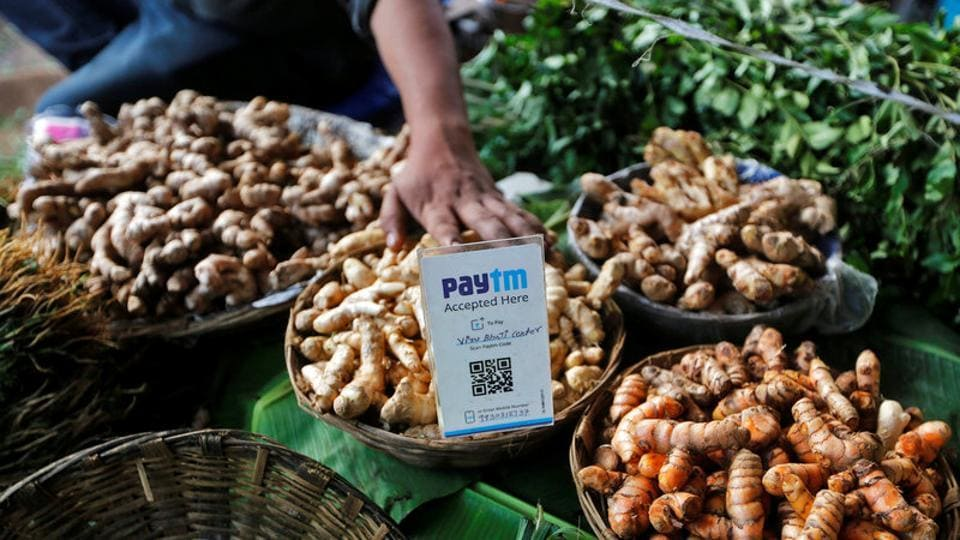 An advertisement board displaying a QR code for Paytm, a digital wallet company, is seen placed amidst vegetables at a roadside vendor's stall in Mumbai on November 19, 2016.