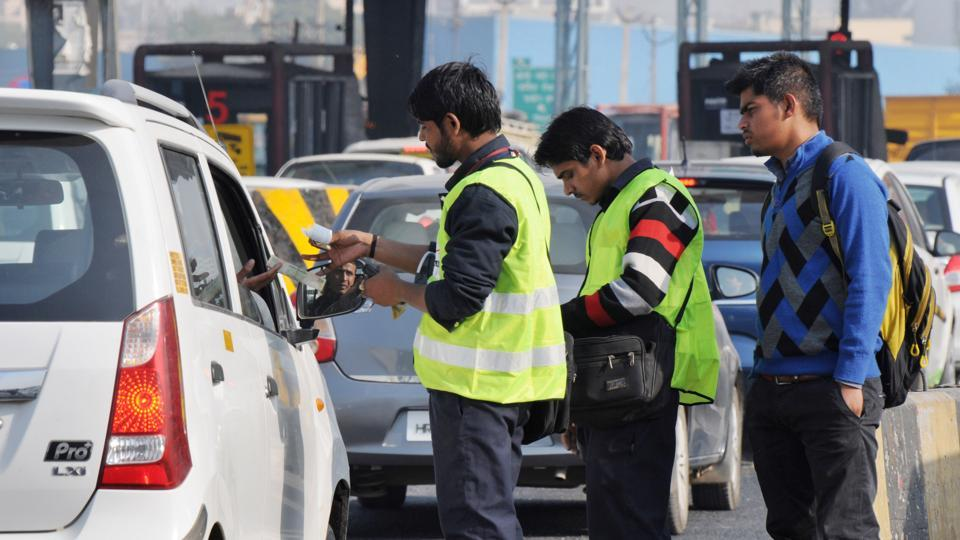 A toll attendant gives a payment slip from a hand held swipe machine to car drivers at the Kherki Daula toll plaza.