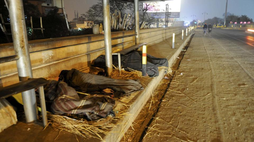 Homeless people sleep by the side of a road  on a winter night in Lucknow. (Deepak Gupta / Ht photo)
