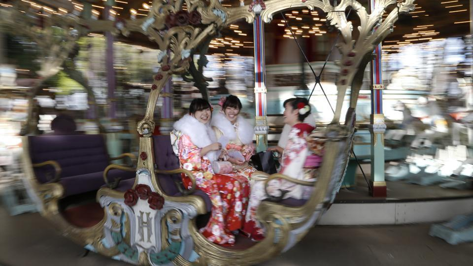 A group of women gets on a merry-go-round.  (AP)