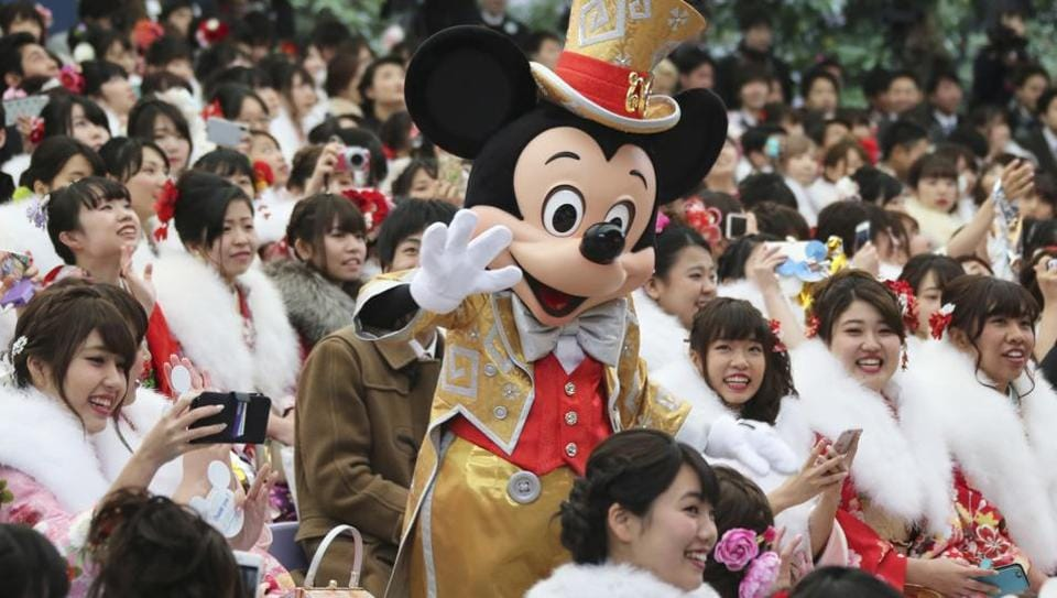 Mickey Mouse waves at the young Japanese who celebrate becoming 20 years old during the coming of age ceremony. (Koji Sasahara / AP)