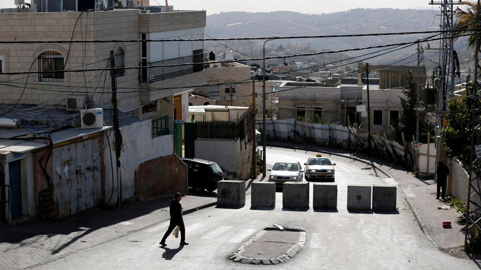A man walks next to a newly erected concrete barriers at the entrance to Jabel Mukaber, in an area of the West Bank that Israel captured in a 1967 war and annexed to the city of Jerusalem, the morning after a Palestinian rammed his truck into a group of Israeli soldiers on a popular promenade in Jerusalem.