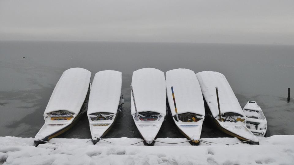 Snow-covered Shikara boats are moored to the bank of the semi-frozen Dal lake in Srinagar. (Waseem Andrabi / HT Photo)