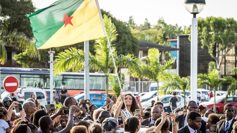 Miss Guyana 2016 and newly elected Miss France 2017 Alicia Aylies, waves a Guiana flag to the crowd as she parades in a car on January 9. (jody amiet / AFP)