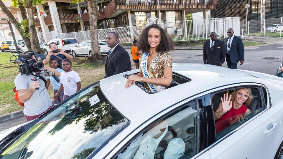 Miss Guyana 2016 and newly elected Miss France 2017 Alicia Aylies looks on and Miss France Society President and Miss France 2002 Sylvie Tellier (down) waves to people as they parade in a car on January 9, 2017 in Cayenne.  (jody amiet / AFP)