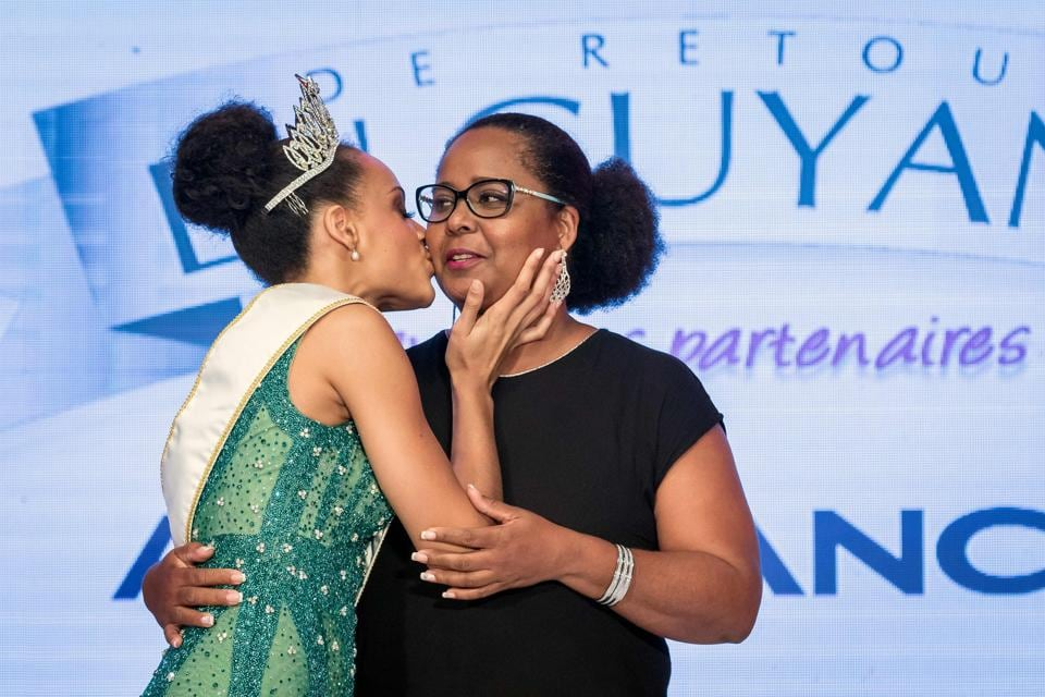 Miss Guyana 2016 and newly elected Miss France 2017 Alicia Aylies (L) kisses her mother on stage during a show on January 9, 2017 in Cayenne.  (jody amiet / AFP)