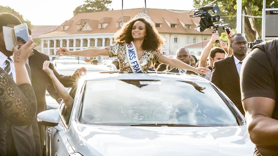 Miss Guyana 2016 and newly elected Miss France 2017 Alicia Aylies, waves to people as she parades in a car on January 9, 2017 in Cayenne. (jody amiet  / AFP)