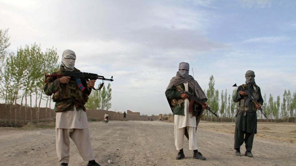 Members of the Taliban stand at the site of the execution of three men in Ghazni province, Afghanistan.