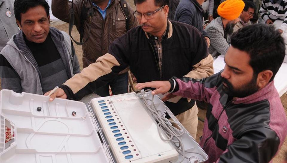 Poll officials checking the machines during distribution in Jalandhar on Monday.