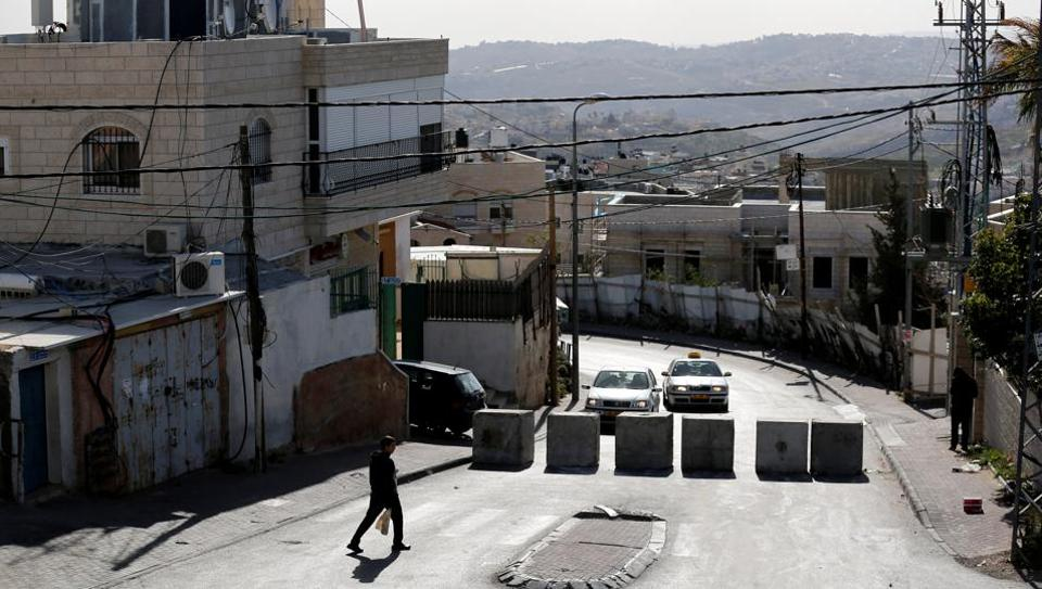 A man walks next to a newly erected concrete barriers in an area of the West Bank.