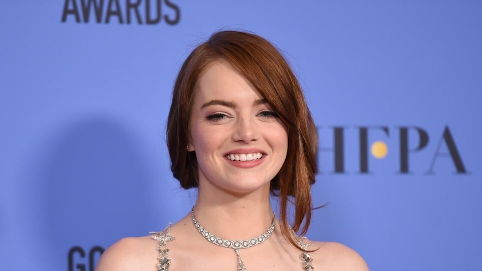 Emma Stone poses with her award for best actress in a musical or comedy for her role in