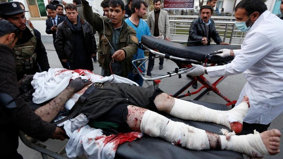 Men carry an injured policeman to a hospital after a suicide attack in Kabul on January 10.