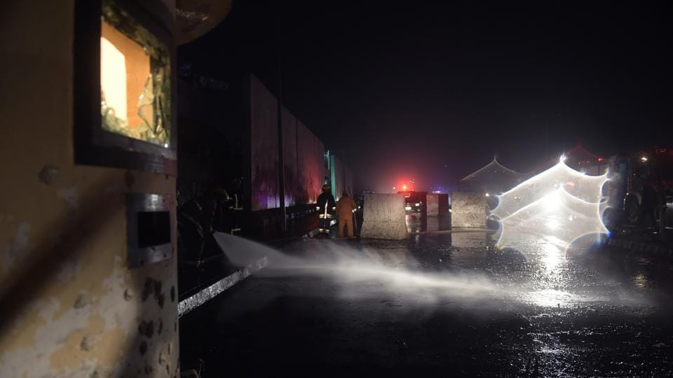 Afghan firefighters clear the road at the site of twin blasts near the Afghan parliament in Kabul on Tuesday.