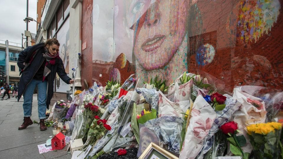 A woman adds a bunch of flowers to the tributes in front of the mural of late British pop icon David Bowie created by Australian street artist James Cochran, also known as Jimmy C, as fans gathered to pay their respects in Brixton, south London on January 10, 2017 on the first anniversary of Bowie's death.