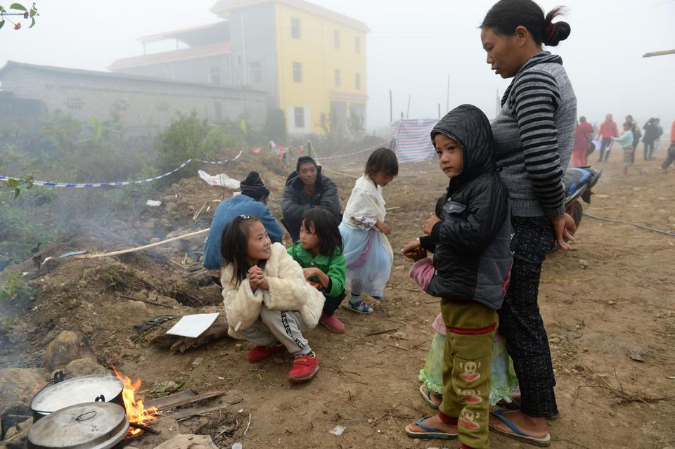 Refugees from Myanmar cooking outside a temporary shelter across the border in Manghai, in southwest China's Yunnan province.
